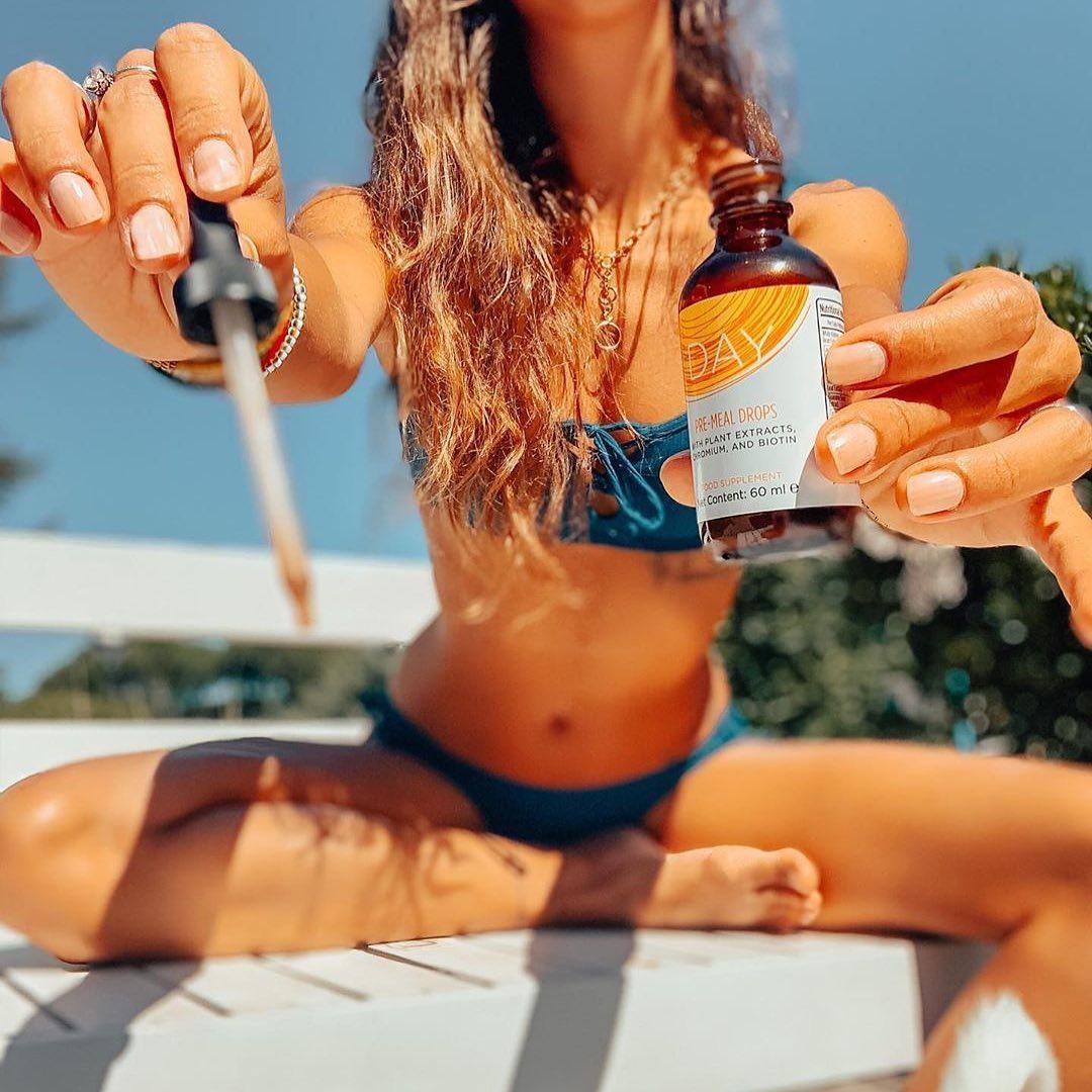 woman holding slenderiix in bikini